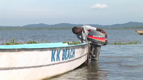 Zoomin-of-a-young-Ugandan-man-attaching-an-outboard-motor-to-a-fishing-skiff