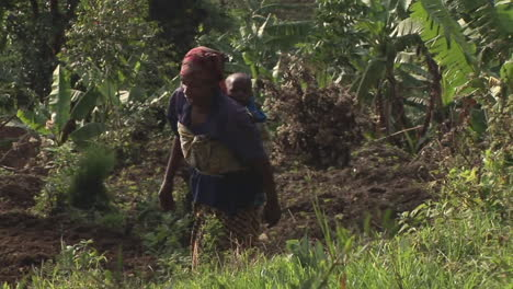 Trackingout-of-an-African-woman-climbing-a-green-hill-with-her-baby-on-her-back