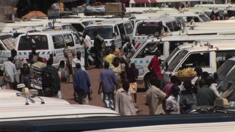 2020-Longshot-of-villagers-carrying-their-shopping-past-vans-in-a-marketplace-in-Kampala-Uganda