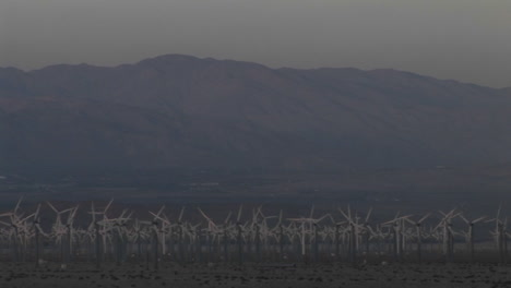 Wind-turbines-spin-against-a-backdrop-of-mountains-in-the-California-desert