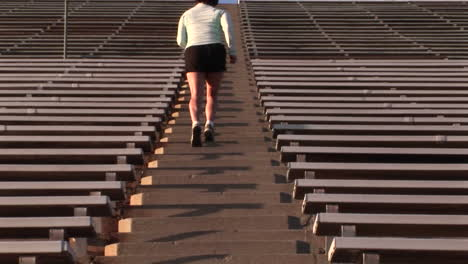 Crab-left-of-a-woman-run-up-the-steps-of-a-large-stadium