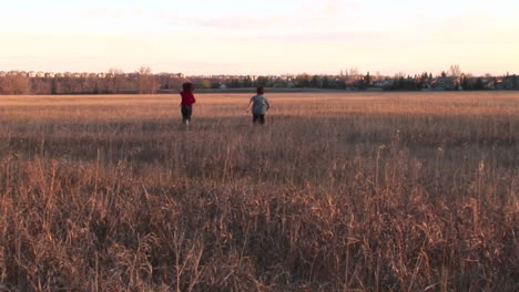 Medium-shot-of-a-boy-and-girl-run-freely-out-into-an-open-field