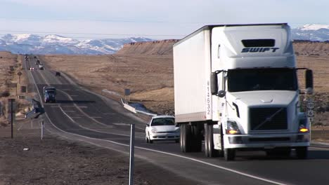 A-semi-truck-moves-along-a-highway-through-the-Rocky-Mountains