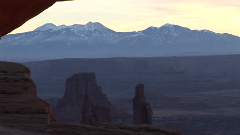 Snowcovered-mountains-with-dramatic-mesas-in-the-foreground-at-Canyonlands-National-Park