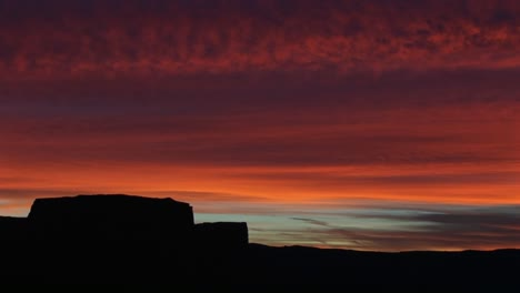A-horizon-of-desert-buttes-and-rock-formations-is-silhouetted-against-a-brilliant-goldenhour-sky