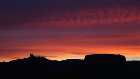A-horizon-of-desert-buttes-and-rock-formations-is-silhouetted-against-a-brilliant-goldenhour-sky-1