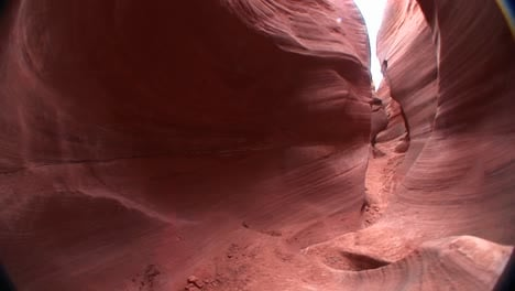 POV-walking-through-a-narrow-passage-between-rock-formations-in-Canyonlands-National-Park