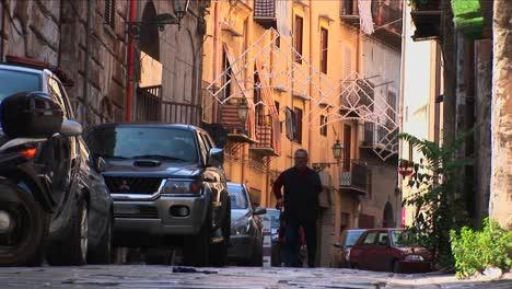 Un-Hombre-Usa-Un-Bastón-Para-Caminar-Por-Una-Calle-Pase-Coches-Alineados-Contra-Los-Lados-De-Los-Edificios-Palermo-Italia