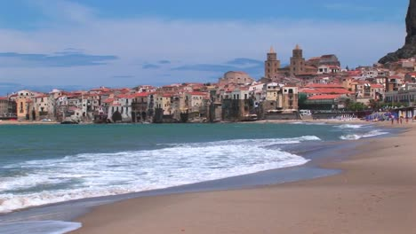 Small-waves-break-near-houses-along-a-shoreline-in-Cefalu-Italy-