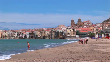 Small-waves-break-near-houses-along-a-shoreline-as-children-play-in-the-sand-in-Cefalu-Italy-