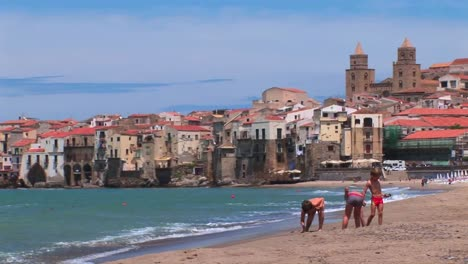 Small-waves-break-near-houses-along-a-shoreline-as-children-play-in-the-sand-in-Cefalu-Italy-1