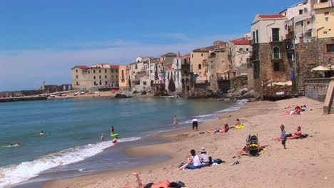 Small-ocean-waves-break-near-houses-as-families-relax-onshore-in-Cefalu-Italy-