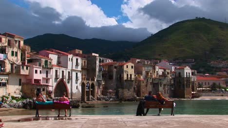 -couples-sit-on-a-benches-overlooking-the-ocean-and-houses-in-Cefalu-Italy-