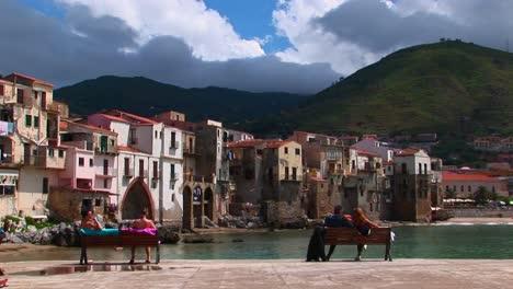 Las-Parejas-Se-Sientan-En-Bancos-Con-Vistas-Al-Océano-Y-Casas-En-Cefalu-Italia