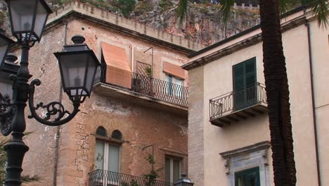 Street-lamps-and-brick-buildings-are-within-close-proximity-of-one-another-in-Cefalu-Italy-