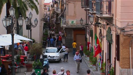 Pedestrians-walk-pass-lamps-and-brick-buildings-within-close-proximity-of-one-another-in-Cefalu-Italy-
