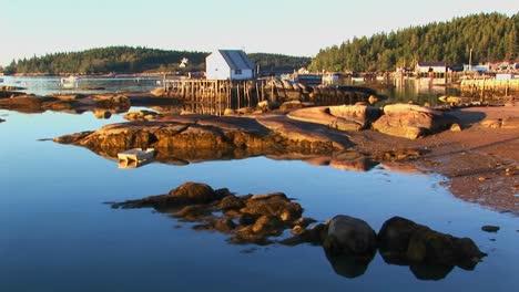 Un-Edificio-De-Aldea-De-Langosta-Sobre-El-Agua-Visto-Desde-Una-Orilla-Rocosa-En-Stonington-Maine