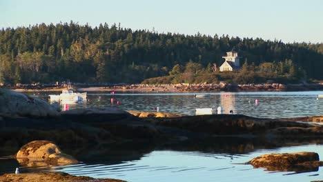 Un-Barco-Anclado-Flota-Cerca-De-Una-Aldea-De-Langostas-Con-Una-Montaña-Cubierta-De-árboles-En-Stonington-Maine