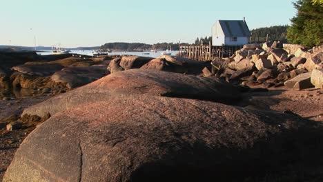 Un-Edificio-En-Una-Aldea-De-Langostas-Está-Sobre-El-Agua-Visto-Desde-Una-Orilla-Rocosa-En-Stonington-Maine