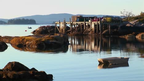 Rocks-and-a-pier-are-near-a-lobster-village-in-Stonington-Maine-at-sunset