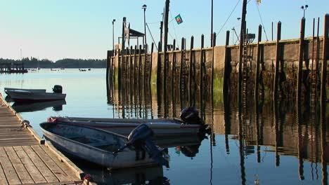 Un-Pueblo-De-Langostas-En-Stonington-Maine-Está-Cerca-De-Un-Muelle-De-Madera-Que-Se-Refleja-En-El-Agua