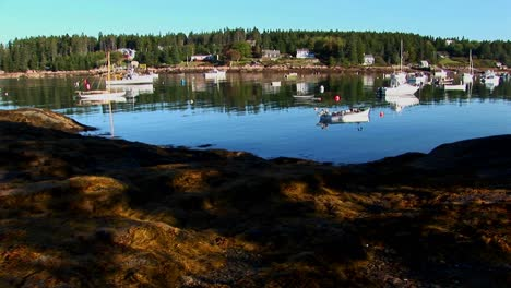 Sailing-boats-are-at-anchor-as-seen-from-the-dirt-shore-of-a-lobster-village-in-Stonington-Maine