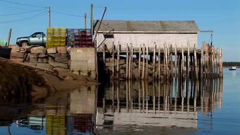 En-Una-Aldea-De-Langostas-En-Stonington-Maine-Pilas-De-Jaulas-Están-Cerca-De-Un-Camión-Estacionado-Fuera-De-Un-Edificio-Sobre-El-Agua