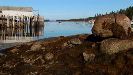 En-Un-Pueblo-De-Langostas-En-Stonington-Maine-Un-Edificio-Está-Sobre-El-Agua-Visto-Desde-Una-Orilla-Rocosa