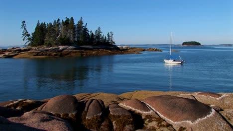 Un-Velero-Está-Anclado-En-Una-Bahía-Frente-A-La-Costa-De-Un-Pueblo-De-Langostas-En-Stonington-Maine
