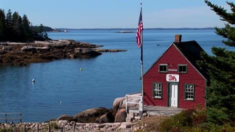 Una-Casa-Roja-Se-Asienta-En-El-Borde-De-Una-Bahía-En-Un-Pueblo-De-Langostas-En-Stonington-Maine