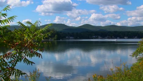 A-glassy-rural-lake-in-Central-Vermont-is-surrounded-by-trees-and-a-cloudy-blue-sky