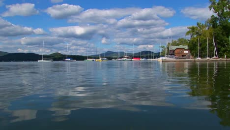 A-cloudy-blue-sky-and-sailboats-are-seen-in-the-distance-of-a-glassy-rural-lake-in-Central-Vermont-