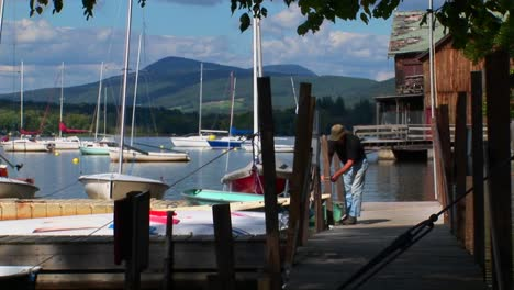 A-man-ties-his-boat-to-a-wooden-dock-on-a-rural-lake-in-Central-Vermont