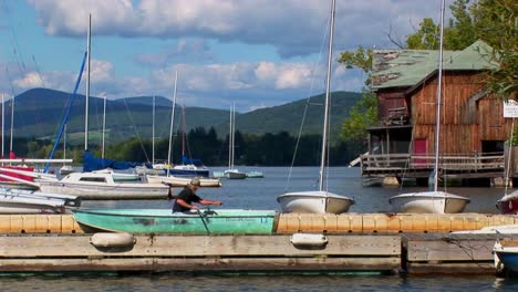 A-man-drifts-in-a-rowboat-near-sailboats-on-a-rural-lake-in-Central-Vermont