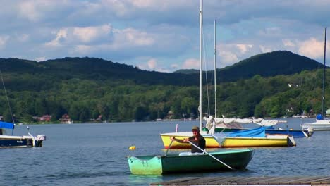 A-man-drifts-in-a-rowboat-near-sailboats-and-a-dock-on-a-rural-lake-in-Central-Vermont-