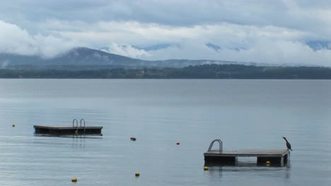 Clouds-cover-a-mountain-range-in-the-distance-of-diving-platforms-on-calm-water-at-Lake-Champlain-in-Vermont