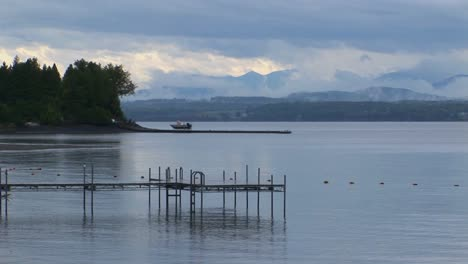 A-small-dock-extends-into-calm-waters-below-a-grey-and-cloudy-sky-at-Lake-Champlain-in-Vermont