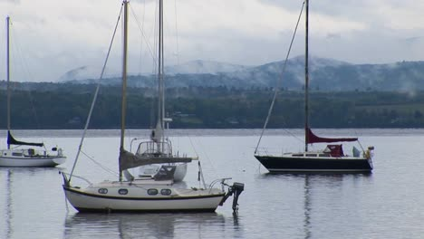 Clouds-cover-a-mountain-range-in-the-distance-of-sailboats-on-calm-water-at-Lake-Champlain-in-Vermont