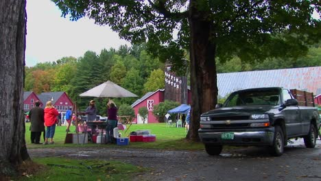 Families-picnic-near-trees-and-red-barns-at-a-Country-Fair-in-Vermont