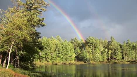 Un-Arco-Iris-Sobre-Un-Bosque-Y-Cerca-De-Un-Lago-En-La-Zona-Rural-De-Maine-1