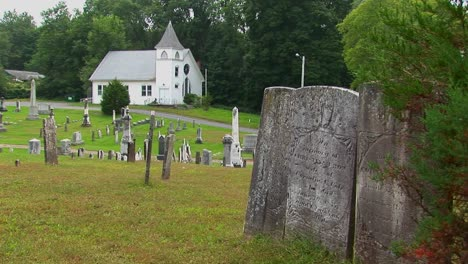 New-England-graveyard-markers-stand-in-an-old-cemetery-near-a-church