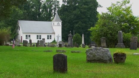 Gravestones-stand-in-an-old-New-England-graveyard-near-a-white-church