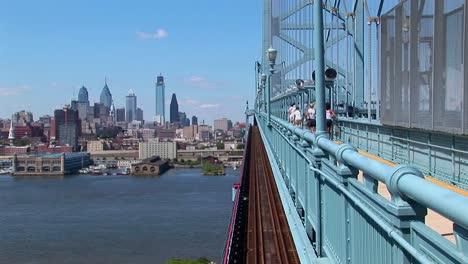 A-group-of-joggers-run-across-the-Ben-Franklin-Bridge-leading-to-Philadelphia-Pennsylvania