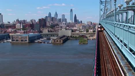 Un-Tren-De-Tránsito-Rápido-Cruza-El-Puente-Ben-Franklin-Alejándose-De-Filadelfia-Pensilvania-1