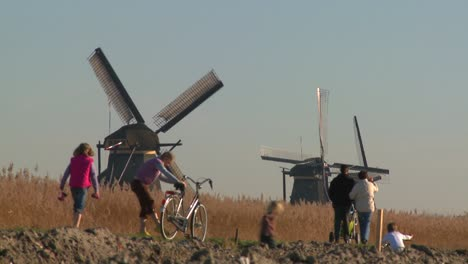 Dutch-citizens-walk-on-a-footpath-in-front-of-windmills-