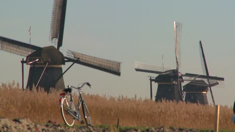 A-bicycle-is-parked-along-a-path-in-Holland-with-windmills-in-the-background
