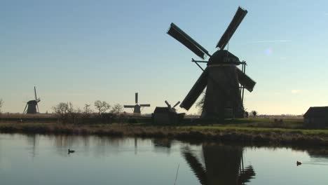 Windmills-line-a-canal-in-Holland-as-ducks-float-by