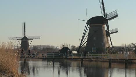 Dutch-citizens-cross-a-footbridge-in-front-of-windmills-along-a-canal-in-Holland