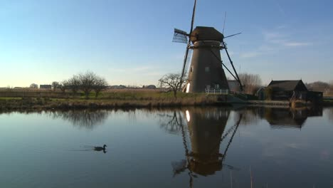 Windmills-line-a-canal-in-Holland-as-ducks-float-by-1