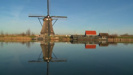 A-windmill-stands-proudly-along-a-canal-in-Holland
